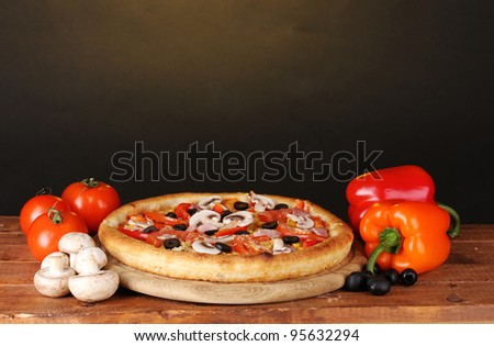 Aromatic pizza with vegetables and mushrooms on wooden table on brown background