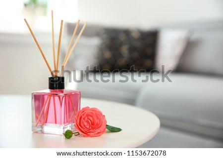 Aromatic reed air freshener and rose on table indoors #1153672078