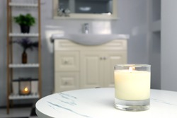 aromatic scented candle glass is put on the white marble table in a luxury white bathroom toilet to creat relax and cozy and clean ambient