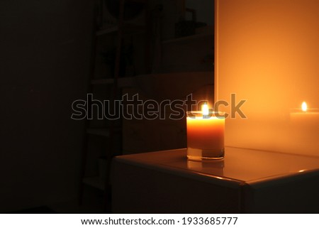 aromatic scented candle glass is put on the white tile shelf in a luxury white bathroom toilet to creat relax and cozy and clean ambient during using Foto d'archivio ©