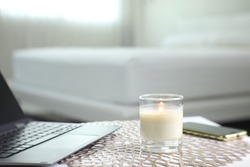 aromatic scented candle is on the table with laptop computer and mobile phone in the white bedroom during self isolation or work from home for preventing infection from coronavirus covid19 pandemic