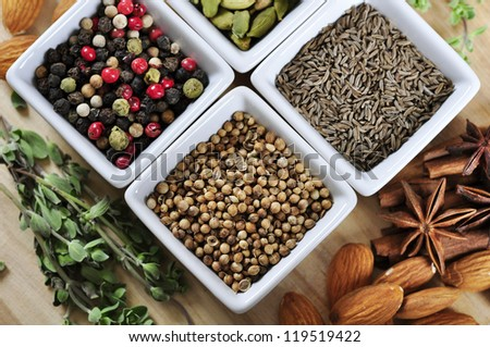Aromatic spices in white bowls on wooden background with nuts and herbs