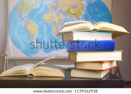 Arranged huge textbooks on desk against background with world map hanging on wall.  #1139562938