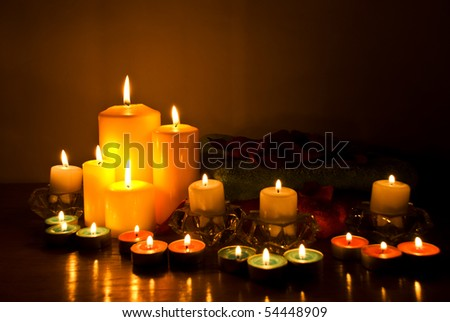 Arrangement for spa with candle lights,towels and petals in darkness on wood table