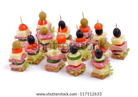 Arrangement of Appetizers with Bacon, Salami, Tomatoes, Cheese, Cucumber, Green Olive, Black Olive, Lettuce and Whole Grain Bread isolated on white background