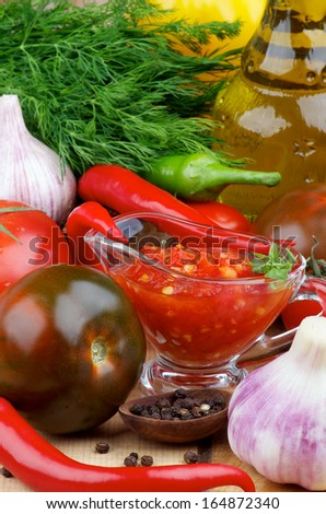 Arrangement of Bruschetta Sauce in Glass Gravy Boat with Black Tomatoes, Garlic, Chili Peppers and Olive Oil in Glass Bottle closeup on Wooden background