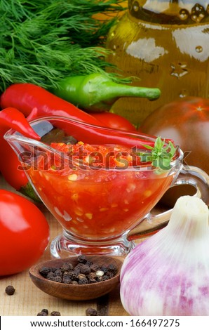 Arrangement of Bruschetta Sauce in Glass Gravy Boat with Black Tomatoes, Garlic, Chili Peppers and Glass Bottle of Olive Oil closeup on Wooden background