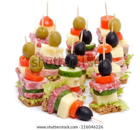 Arrangement of Canape with Bacon, Salami, Tomatoes, Cheese, Cucumber, Green Olive, Black Olive, Lettuce and Whole Grain Bread isolated on white background - stock photo