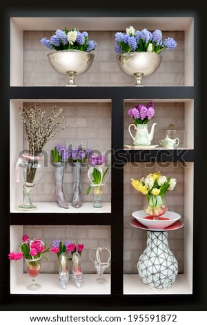 Arrangement of flowers in a vase on the shelf - Shutterstock ID 195591872