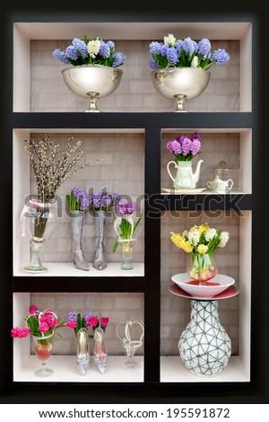 Arrangement of flowers in a vase on the shelf - Shutterstock ID 195591872