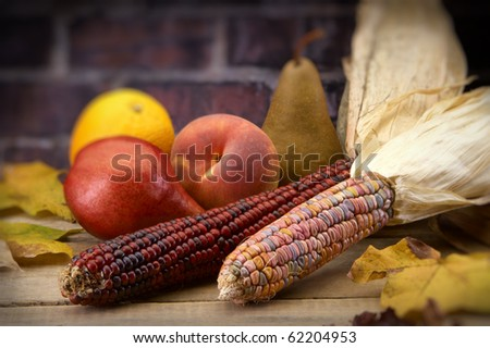 Arrangement of fruit and Indian corn on wood table