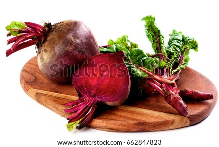 Arrangement of Full Body, Half and Young Sprouts of  Fresh Raw Organic Beet Roots with Green Beet Tops on Wooden Cutting Board isolated on White background