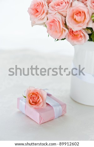 Arrangement of pink roses for holiday and a gift box