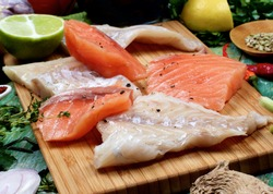 Arrangement of Raw Fillet of Salmon and Cod, Greens, Spices and Citrus Fruits closeup on Wooden Cutting Board. Focus on Foreground
