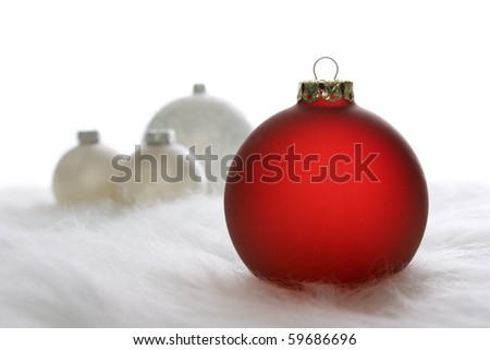 Arrangement of red and white Christmas baubles on white fur