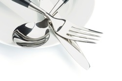 Arrangement of Silverware with Table Knife, Spoon and on White Plate isolated on white background