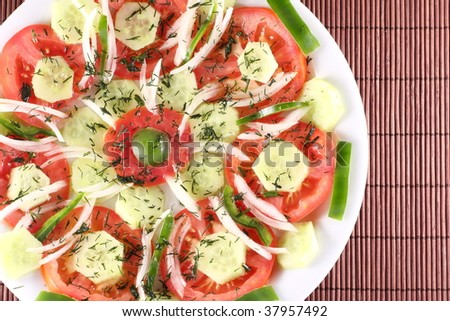 Arrangement of vegetable salad (Tomato, cucumber, green capsicum, onion and a slice of olive) - stock photo