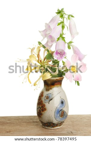 Arrangement of wild flowers in a decorated pot on a wooden bench