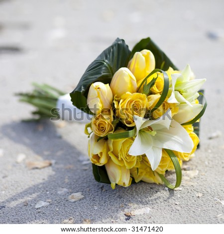 arrangement of yellow roses and lilies on the beach