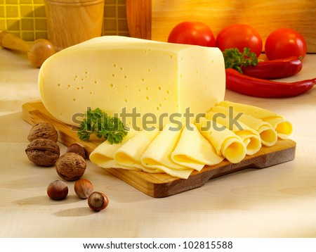 Arrangement with appetizing cheese on the kitchen cutting board.