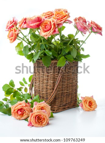 Arrangement with roses in a wicker basket in the orange colors on a white background