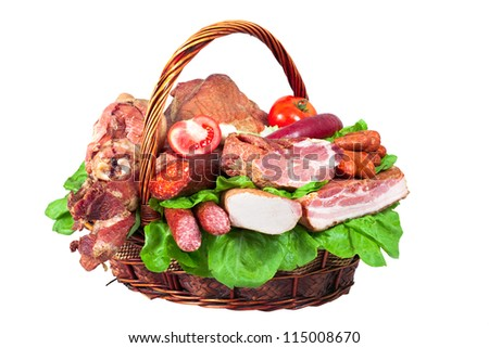 Arranging dried meat with bacon and sausages in wooden basket isolated on white background