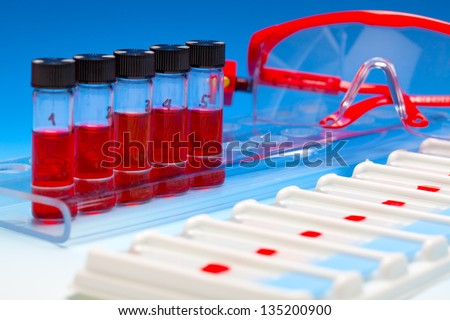 Array of blood samples for microscopy and biopsy tissue on blue gradient background