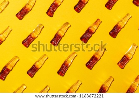 Array of cola bottle shaped gummy candies against saturated yellow background. #1163672221