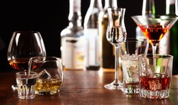 Array of different alcoholic beverages served in glasses on a wooden bar counter with backdrop of liquor bottles in a panorama format