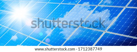 Array Of Solar Panels With Blue Sky And Sunlight Reflection- Clean Energy Concept Photo stock ©