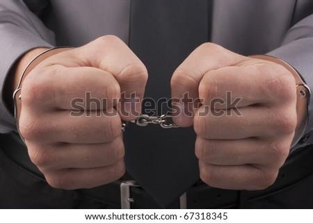Arrest, close-up shot man's hands with handcuffs.