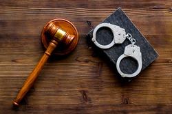 Arrest concept. Handcuffs near judge gavel on dark wooden background top-down