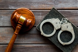 Arrest concept. Handcuffs near judge gavel on dark wooden background top-down