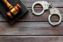 Arrest concept. Handcuffs near judge gavel on dark wooden background top-down copy space