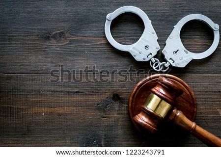 Arrest concept. Metal handcuffs near judge gavel on dark wooden background top view copy space