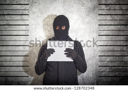 Arrested burglar. Thief with balaclava caught and arrested in front of the grunge concrete wall.