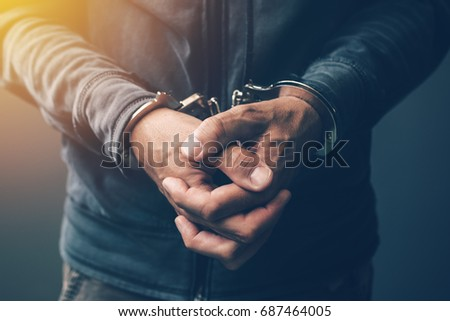 Arrested computer hacker and cyber criminal with handcuffs, close up of hands