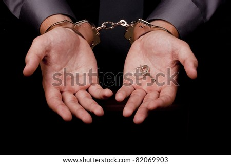Arrested in handcuffs in his hands the key to the handcuffs.
