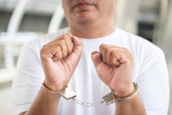 arrested man criminal gets locked up by handcuff; crime scene investigation with man getting arrested with handcuff; concept of crime, public order, safety, law enforcement; old asian man model
