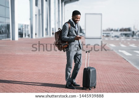 Arrival at Airport. Businessman Checking E-mail On Mobile Phone, Standing with Baggage Outdoors Photo stock ©