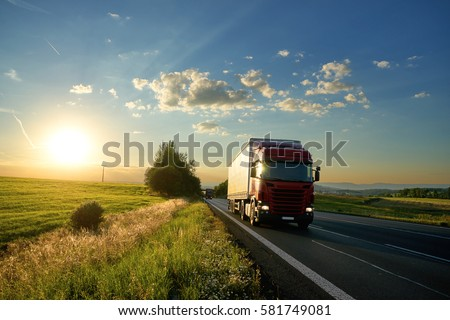 Arriving red truck on the road in a rural landscape at sunset