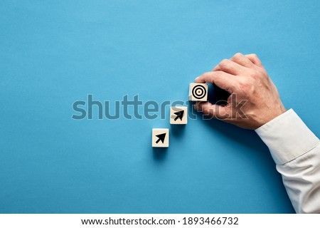 Arrow and target symbols on wooden blocks with a businessman hand placing the target symbol. Goal or agenda setting in business concept.