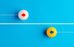 Arrow icons in contrast on table tennis balls moving towards opposite directions. Competition, diversity, opposition or confrontation concept.