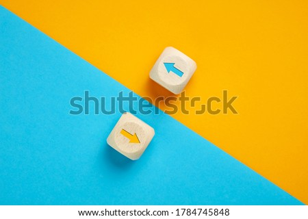 Arrow icons in contrast on wooden cubes moving towards opposite directions. Competition, diversity, opposition or confrontation concept.  Foto stock ©