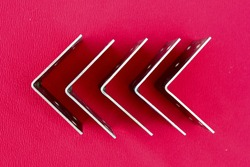 Arrow made of brackets isolated on pink. Metal corners are directed to the left with a place for the text. Golden metal bracket on a red background. Metal corners frames, borders. Isolated.