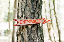 Arrow-pointer with the inscription Entrance hangs on a tree. Title: Entrance