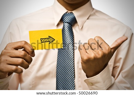 Arrow shape on yellow card and hand gesture by businessman.