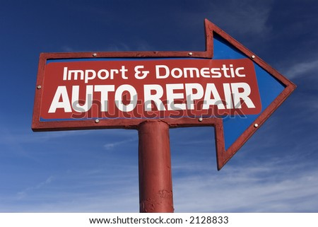Arrow Shaped sign for auto repair shop against blue sky.
