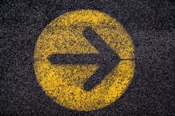 arrow sign in yellow circle painted on black asphalt