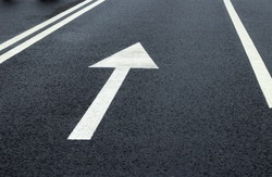 Arrow sign on the road. White arrow on the asphalt. White forward arrow on a blurry street background